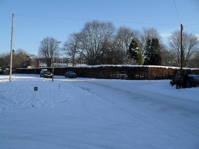 Approaching the junction of a snowy High Lawn Way and Broadmere Avenue