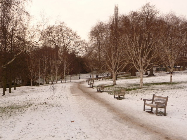 Hyde Park: line of benches by snowy path