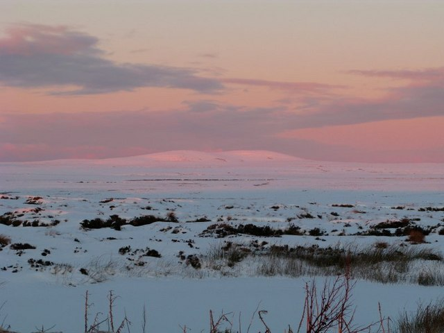 A snowy Muirneag reflecting the setting sun