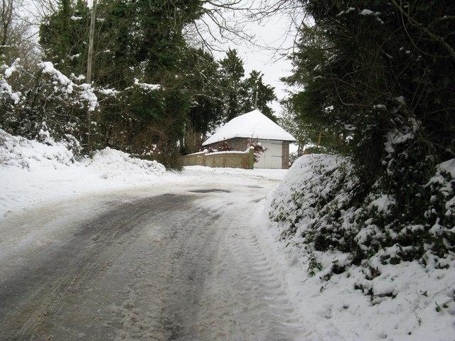 Private garage facing sharp bend in Madehurst