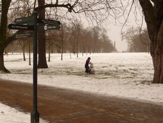 Kensington Gardens: a signpost and a snowman in progress