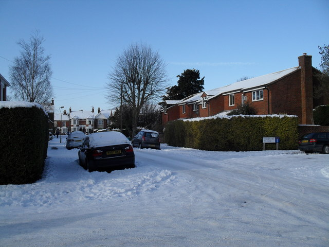 Approaching the junction of a snowy First Avenue and Carisbrooke Close