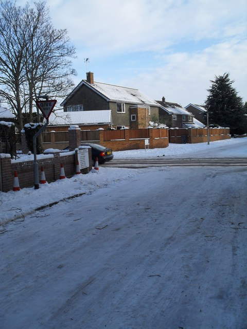 Approaching the junction of a snowy First Avenue, Southleigh Road and Hallett Road