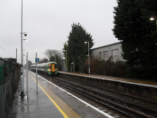 Train from Brighton arriving at a very wet Angmering Station