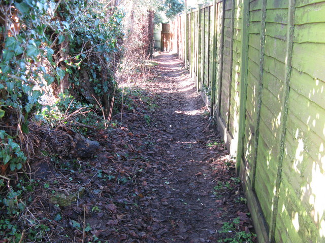 Footpath west between Churchfield Farm on the left and houses in Holly Close at West Chiltington