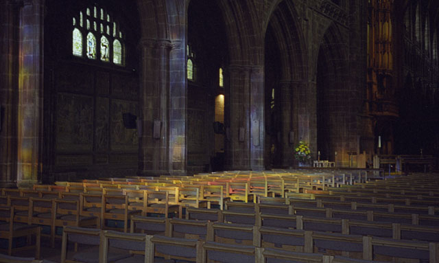 Coloured light illuminating chairs in Chester Cathedral