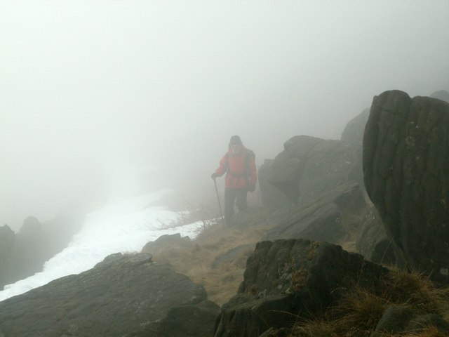 A walker appearing from the moorland clag.