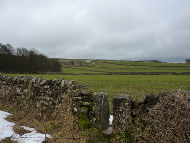 Stile, fields and a barn on the hillside