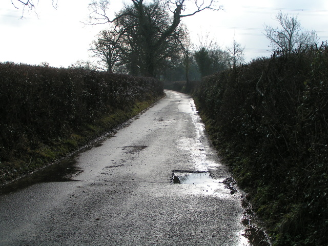 A wet lane with partially repaired road surface