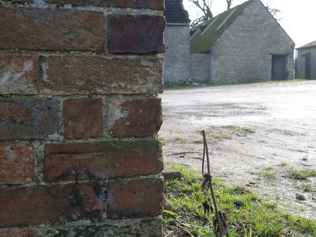 Bench mark at the base of a farm building in Deene