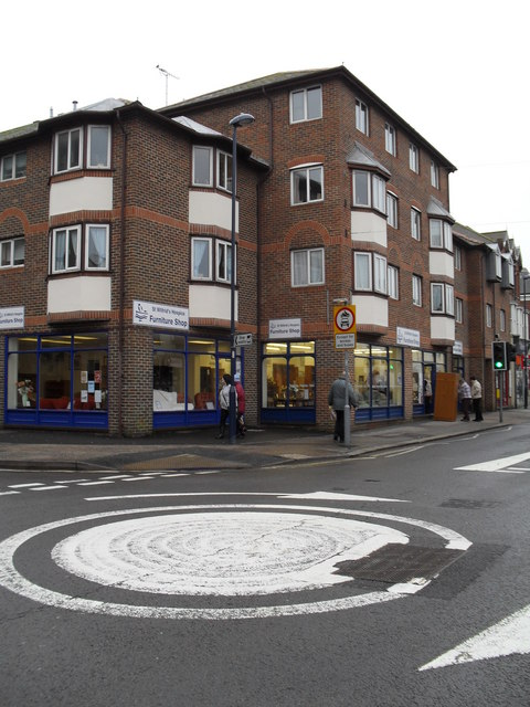 Looking across the mini-roundabout towards a charity shop