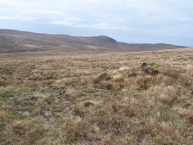 Peat covered cairn on featureless moorland hillside in Strath Chailleach