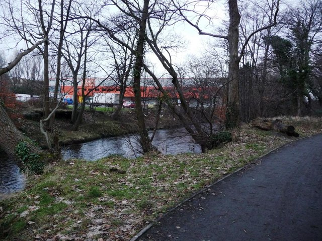 Water of Leith Walkway, with Booker's orange warehouse behind the trees