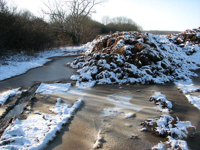 Frozen manure heap surrounded by frozen puddles