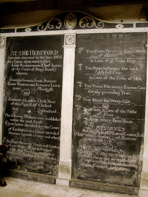 A carved record of the judgement in a tithe dispute, in a darkened corner of Clodock Church