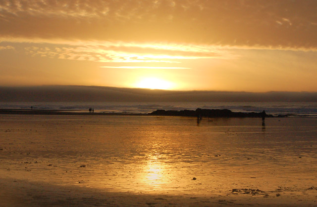 The sun setting over Gwithian beach at low water