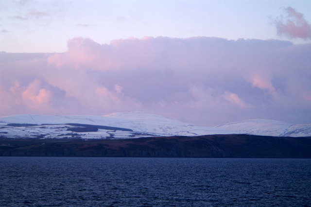 Sunset rays redden the snow on Snaefell, beyond Onchan Head