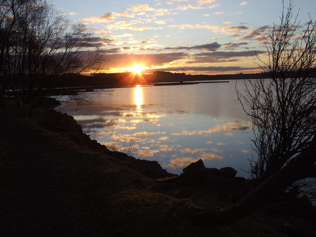 Sun setting over Loch Fitty, sky reflected in the water, and some bare trees in the foreground
