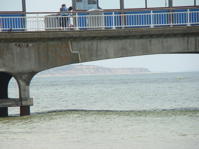 View of cliffs from the beach, looking through the pier