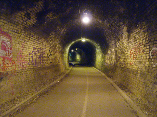 graffiti inside a brick-lined tunnel -- we can just see the mouth of the tunnel ahead