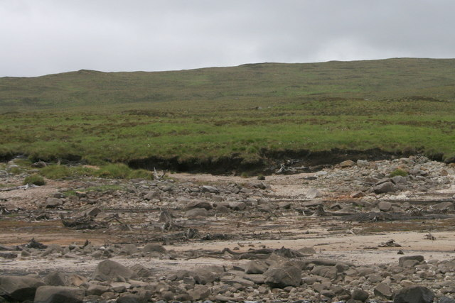 A burn enters Loch Shin in a desolate spot