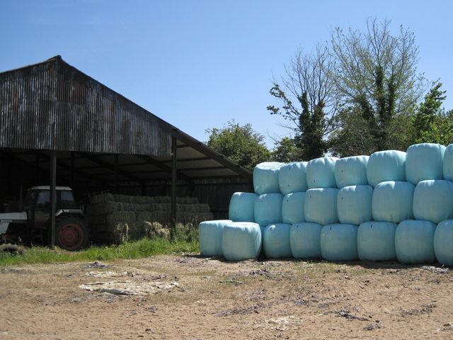 Bales in aqua by a barn