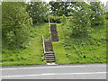 Dist:0.9km<br/>The footpath crosses the A494 near Mynydd Isa, via two sets of steps. This is looking from the northern side towards the other embankment.