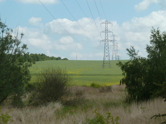 Field by the motorway with line of pylons