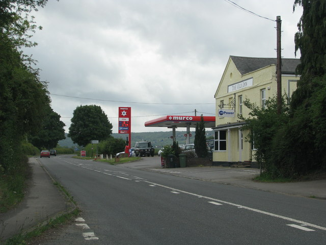 The A40 passes a garage and disused pub in Postcombe