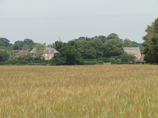 Uggeshall Hall and the nave of the church across a barley field