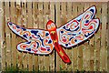 Dist:0.3km<br/>This is one of the many colourful butterfly and dragonfly shapes fixed to a timber fence at a community space/garden area at Drongan. For a wider view of the fence, see [[[2550163]]].