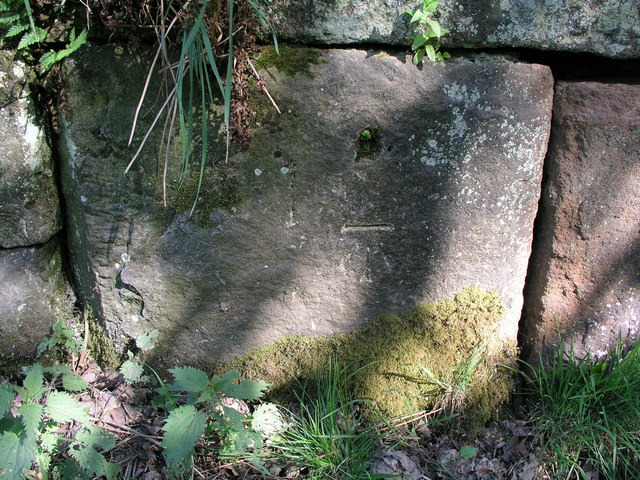 Cut bench mark on old abutment in Lees Road, Birchover