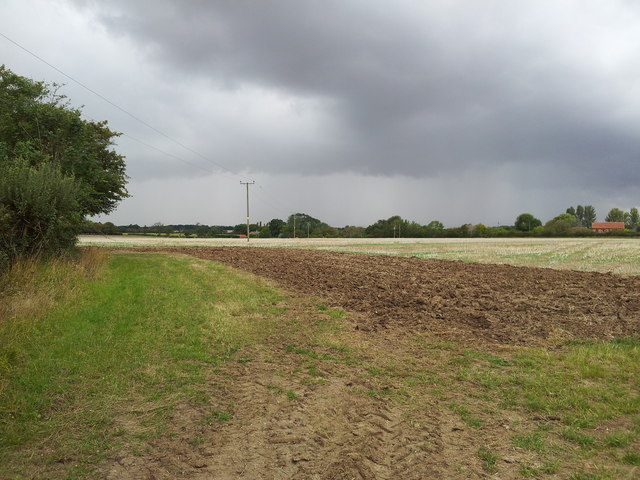 Newly ploughed fields under storm clouds