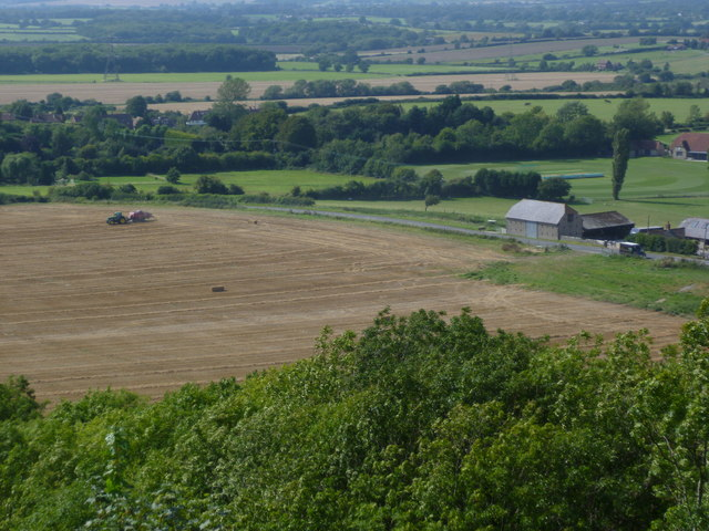 Tractor at work in stubble field by Wickhurst Barns
