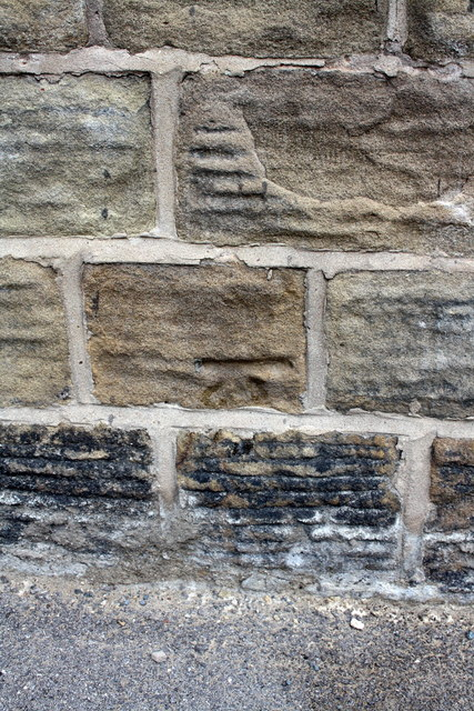 Weathered benchmark on Hopwood St  wall of #18 Huddersfield Road