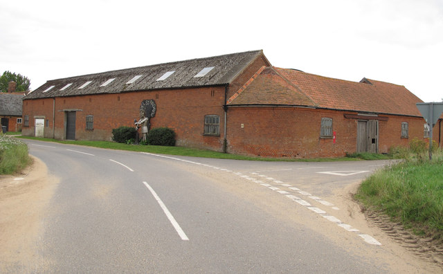 Village sign on farm building near road junction