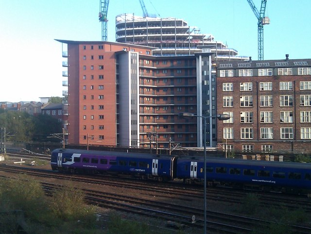 Train passing new apartments on approach to Manchester Victoria