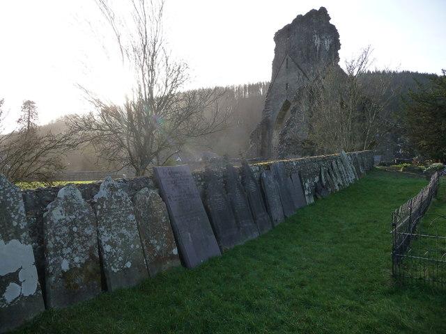 Gravestones against the church wall near Talley Abbey ruins