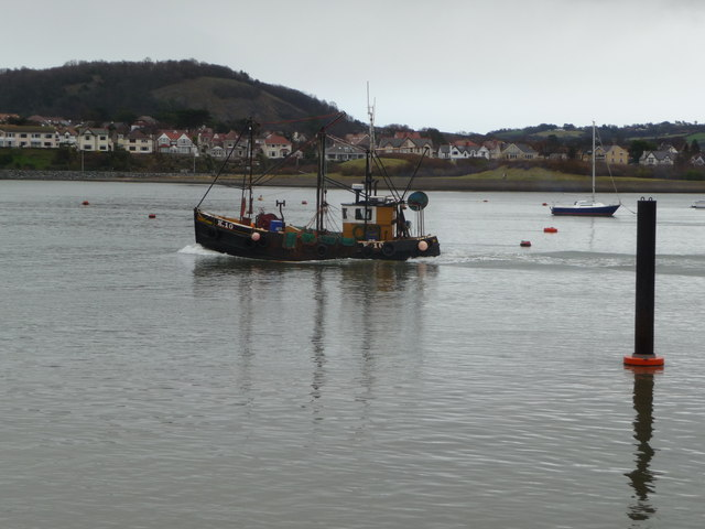 Boat heads down the Afon Conwy towards the sea