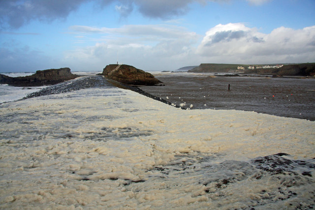 Foam-covered breakwater at Bude