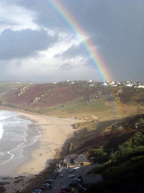 Sun and rainbow on Sennen beach