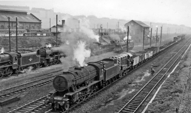 WD 2-8-0 hauling a new Diesel shunter in Up freight passing Balornock Locomotive Depot