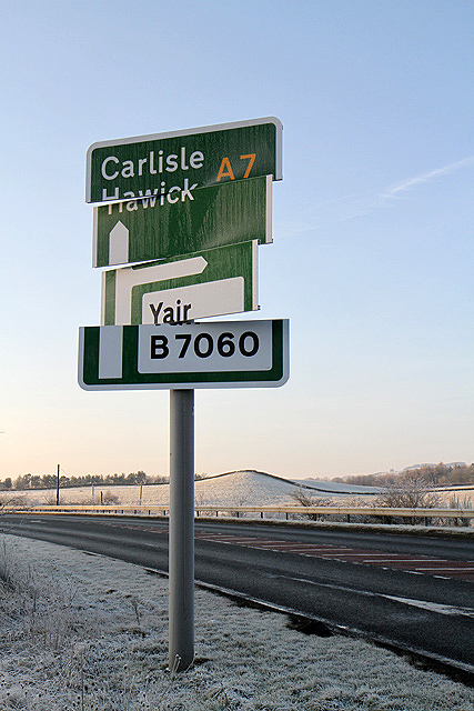 A wind-damaged sign on the A7