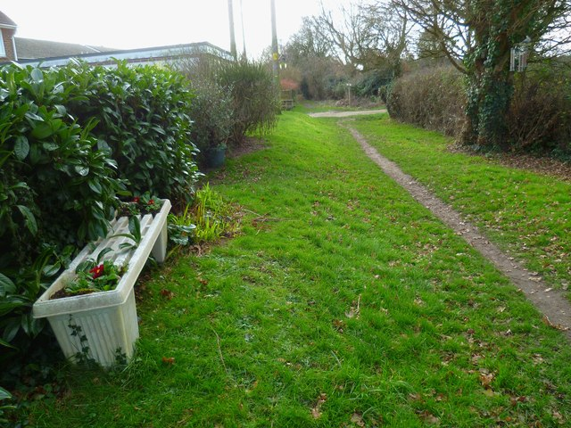 Seat with flowers provided on footpath at Hunston