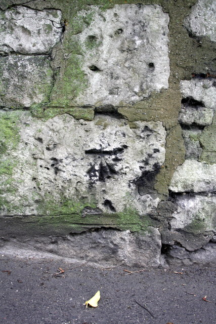Benchmark on wall of New Road