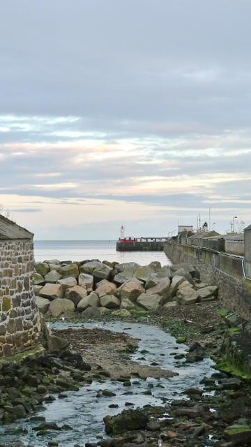 The Newlyn River meets the sea behind the Fish Dock Wall