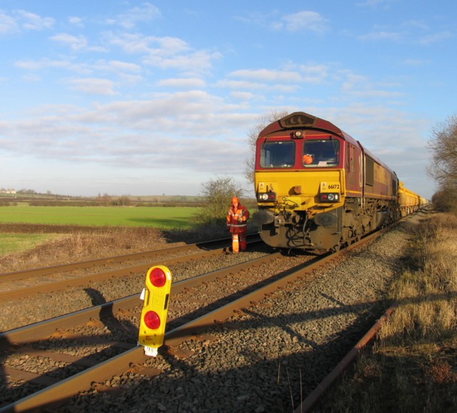 Ballast train hauled by 66 172 parked next to Wyfordby level crossing