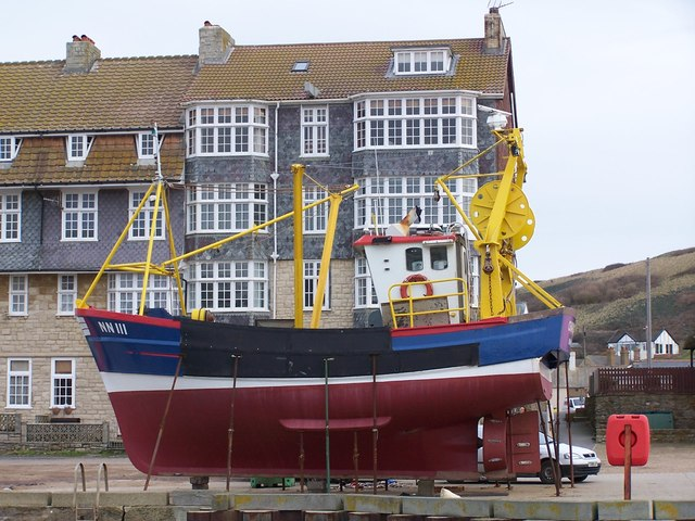 Fishing boat and quayside housing, West Bay