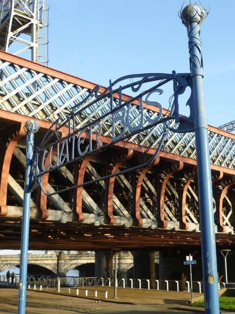 The image shows a wrought steel sign between two lamp posts, forming what used to be where one could approach the river to board the water bus. The metal is painted blue. There's a bridge in the background, making it a little hard to read the sign, with reddish and white-ish structural elements. The cement river walk path is visible running behind the Water Bus sign, and under the bridge.