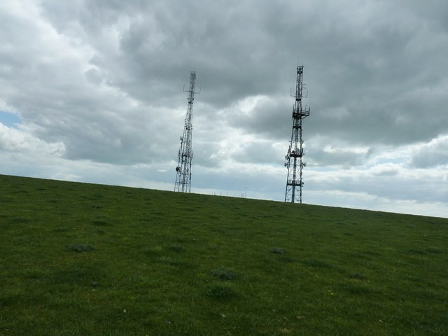 Radio masts silhouettes against a blackening sky